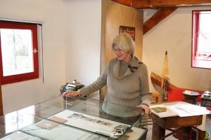 Erika Porten an der Vitrine mit alten Fotoaufnahmen von vor 60 Jahren